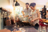 Mixed group of friends have fun while cooking a meal in kitchen - 208969210