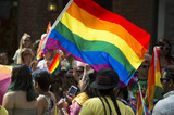 Participants wave rainbow flag and celebrate in the annual Pride Parade as it passes through Greenwich Village. poster