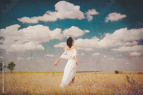Foto Murales photo of beautiful young woman standing in the field on the wonderful sky background