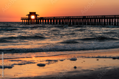 Aluminium Napels Naples, Florida red tide and orange sunset in gulf of Mexico with sun setting inside Pier, framing by wooden jetty, with birds flying over horizon and dark blue ocean waves