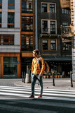 The guy crosses the street through the pedestrian crossing. Stylishly dressed man with a briefcase in a hurry to work and study. The man travels to the cities of .Europe. Poland Warsaw.