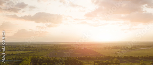 Aerial view from the drone, a bird's eye view of abstract geometric forms of agricultural fields with a dirt road through them in the summer evening at sunset. - 208981023