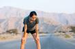 Leinwanddruck Bild - Runner taking a rest on a desert road