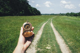 Man with compass in hand on rural road. Travel concept - 208982074