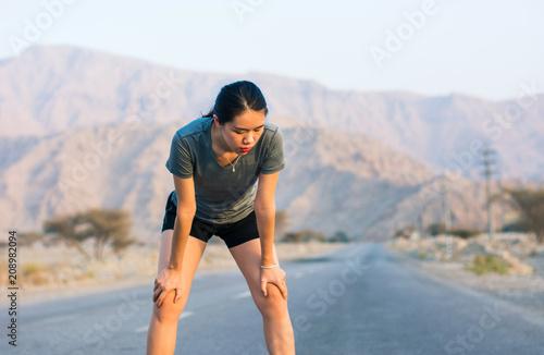 Leinwanddruck Bild Runner taking a rest on a desert road