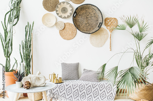 Leinwandbild Motiv Modern minimal home interior design. Pillows, golden teapot, decorative straw plates, Scandinavian blanket, tropical palm tree, succulent and decorations.