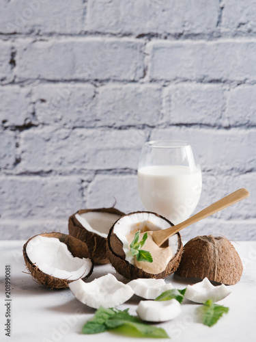 Coconut milk with broken coconut and mint leaves on white table