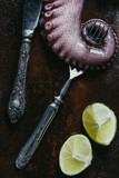 top view of big octopus tentacle with fork, knife and limes on rusty metal surface - 208993865
