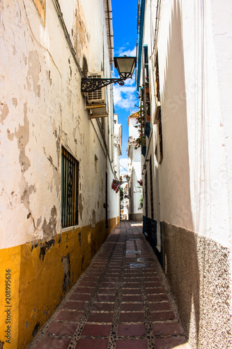 Fotobehang Smalle straatjes Street. A sunny day in the street of Marbella. Malaga province, Andalusia, Spain. Picture taken – 12 june 2018.