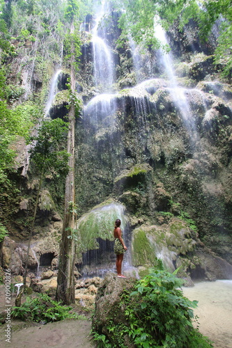 Female model in a green dress looking up at a beautiful cascading waterfall - 209002826