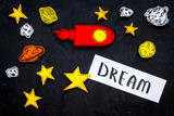 Dream concept. Hand lettering dream at black cosmos background with rocket and stars top view - 209004032