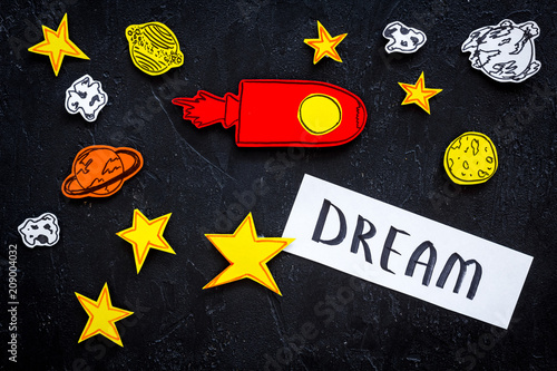 Canvas Heelal Dream concept. Hand lettering dream at black cosmos background with rocket and stars top view