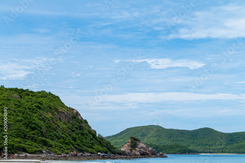 Fotobehang Tropical strand Golden sand beach, Beautiful white clouds on blue sky over calm sea with sunlight reflection and the island is full of trees.