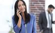 Leinwanddruck Bild - Attractive brunette businesswoman talking on mobile phone