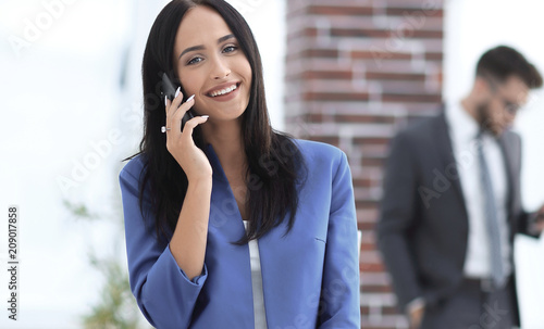 Leinwanddruck Bild Attractive brunette businesswoman talking on mobile phone