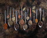 Different spices in  spoons on a vintage background. - 209025214