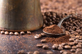 Black roasted coffee grains and ground coffee in spoon. - 209025481