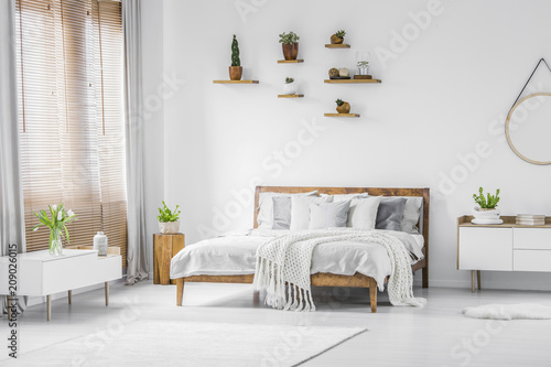 Wooden shelves with plants above a comfortable double bed in a spacious apartment room interior with white furniture and walls