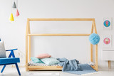Wooden DIY bed in modern child's bedroom interior with blue armchair and posters