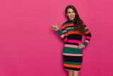 Smiling Beautiful Woman In Multicolored Striped Dress Is Pointing - 209026830