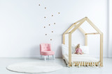 Pink chair against white wall with stickers in simple kid's bedroom interior with wooden bed. Real photo - 209027275