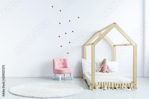 Różowy krzesło przeciw białej ścianie z majcherami w prostym dzieciaka sypialni wnętrzu z drewnianym łóżkiem. Prawdziwe zdjęcie