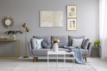 Grey sofa with pillows and blanket standing in bright living room interior with gold lamp, fresh flowers on white table and carpet on the floor
