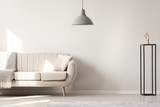 Real photo of a white sofa with cushion and blanket standing next to a black ornament with a wooden hand and a hanging lamp in a simple living room interior - 209028642