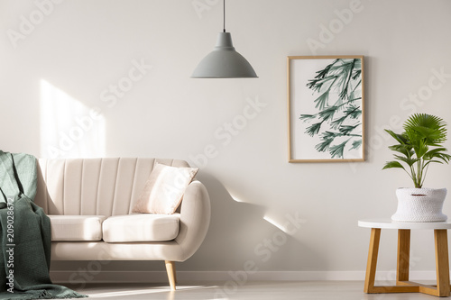 Fotobehang Hoogte schaal Real photo of a couch with blanket and pillow standing next to a table with plant in a beige living room interior with a hanging lamp and poster on a wall