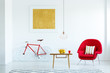 Real photo of a bright living room interior with a red armchair, wooden table with lemons in the basket, lamp, bike and painting on the wall