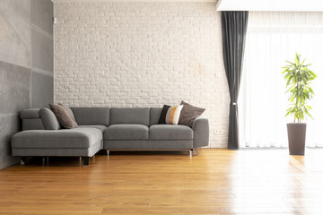 Grey corner couch on wooden floor against brick wall in bright apartment interior with plant. Real photo