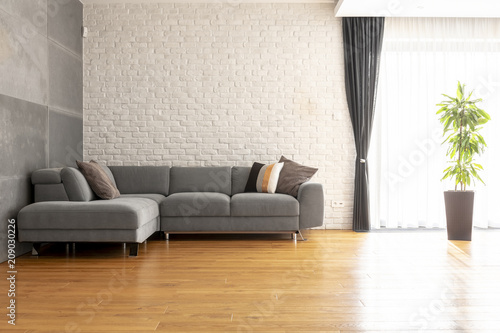 Foto Murales Grey corner couch on wooden floor against brick wall in bright apartment interior with plant. Real photo