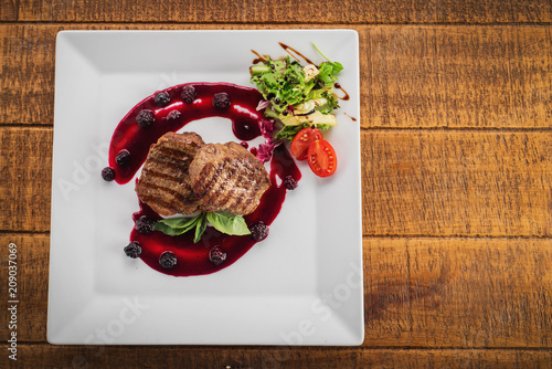 Grilled meat steak with raspberrie sauce on wooden background