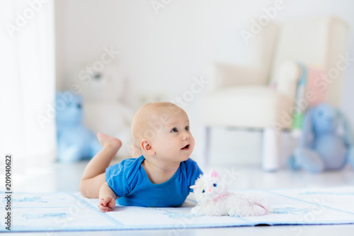 Baby boy playing and learning to crawl