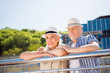 Leinwanddruck Bild - Portrait of attractive cheerful couple in straw hats casual outfit enjoying beautiful view lean on balcony railing looking away spending time together. Vacation weekend holiday concept