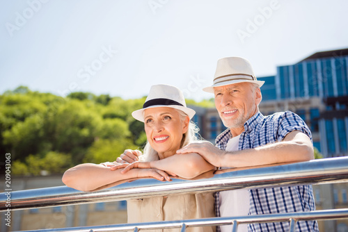 Leinwanddruck Bild Portrait of attractive cheerful couple in straw hats casual outfit enjoying beautiful view lean on balcony railing looking away spending time together. Vacation weekend holiday concept