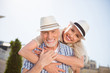 Leinwanddruck Bild - My sweetheart! Portrait of cheerful positive couple with beaming smiles in straw hats, attractive man carrying on back charming woman, enjoying time together outdside