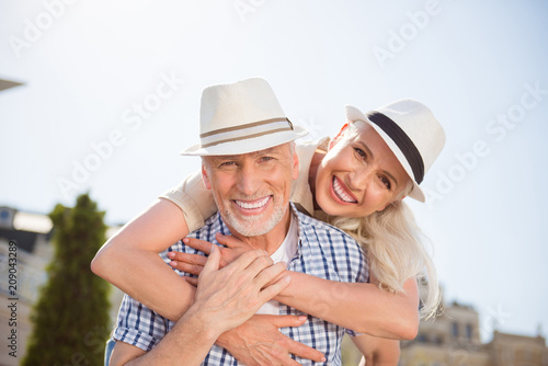 Leinwanddruck Bild My sweetheart! Portrait of cheerful positive couple with beaming smiles in straw hats, attractive man carrying on back charming woman, enjoying time together outdside