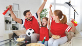 family of fans watching a football match on TV at home. - 209044000