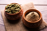 elaichi or Cardamom powder in bowl or heap over moody background with pods. selective focus  - 209048826