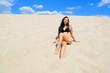 Sexy naked brunette girl in lingerie lying on the sand in the desert.