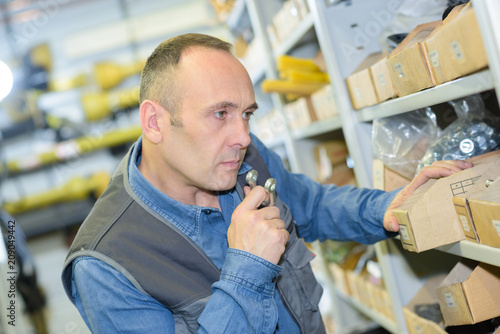 man in warehouse is checking inventory levels of goods
