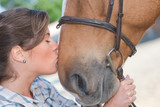 Woman kissing horse's nose - 209050426