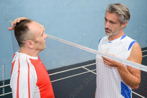 Men in discussion over sports net