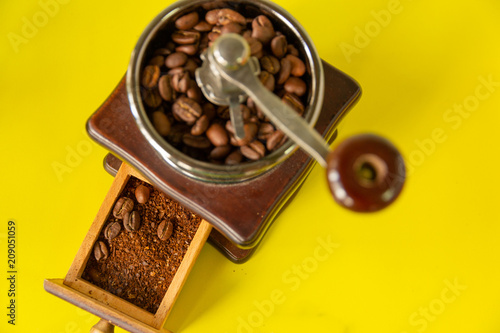 Fotobehang Koffiebonen select focus coffee beans in vintage wooden coffee grinder on yellow background