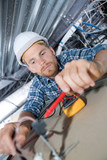 Electrician testing spotlight with multimeter - 209053465