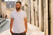 Leinwanddruck Bild - Hipster handsome male model with beard wearing white blank t-shirt with space for your logo or design in casual urban style