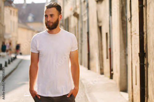 Leinwanddruck Bild Hipster handsome male model with beard wearing white blank t-shirt with space for your logo or design in casual urban style