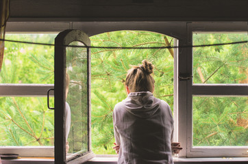 A woman standing by the window admires a view of nature in the countryside