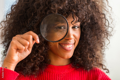 Leinwanddruck Bild Curious african american woman looking through magnifying glass with a happy face standing and smiling with a confident smile showing teeth